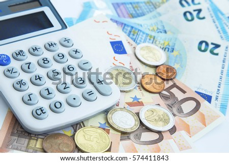 Finance and accounting concept.Money coins and banknotes with calculator