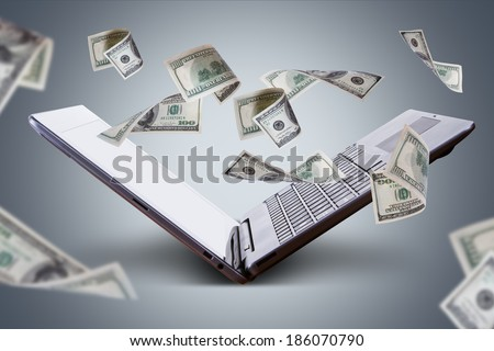 Finance and earning concept, one hundred dollar banknotes flying around laptop, internet, side view on dark background. - stock photo