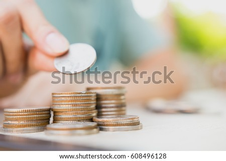 Finance,business and banking concept.Money coin on stack with blur hand putting coin background. concept in grow for success in business and financial