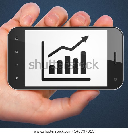 Finance concept: hand holding smartphone with Growth Graph on display. Generic mobile smart phone in hand on Dark Blue background.