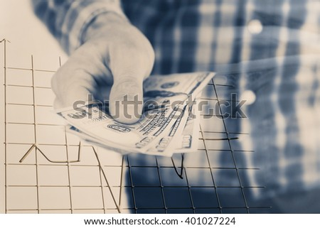 Finance concept. Man holding dollars in hand - stock photo