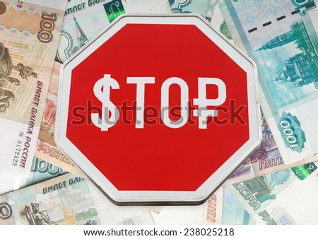 Finance concept with USD and Russian money symbols on a stop road sign over rubles banknotes background   - stock photo
