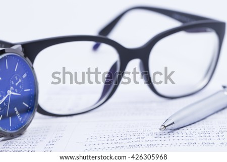 Finance Concepts, pen, watch and glasses with passbook as background