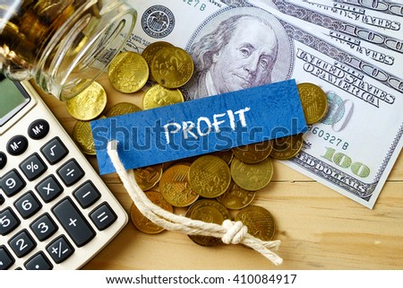 Finance conceptual image with PROFIT words, hundred dollar bills, golden coins and calculator on wooden background.