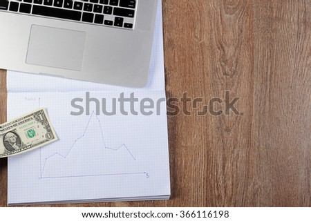 finance crisis diagram notebook with graph schedule  dollars money laptop on wood table - stock photo