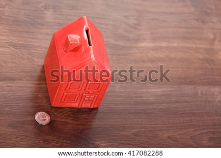 Finance mortgage housing real estate savings concept. House like cash box. Piggy bank in home shape with coin. - stock photo