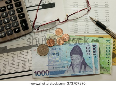 finance sheet with korean money and calculator as background. - stock photo