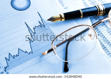 finances and economical background.Statistic, graphics and glasses in blue toned - stock photo