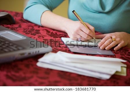 Finances: Anonymous Woman Writing Checks - stock photo
