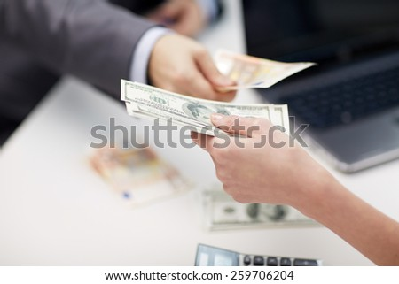 finances, currency, exchange rate, business and people concept - close up of male and female hands giving or exchanging money at office - stock photo