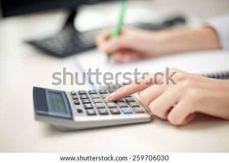 finances, economy, technology and people concept - close up of woman hands with calculator counting and taking notes to notebook