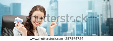finances, people, savings and investment concept - happy business woman with euro cash money over singapore city background - stock photo