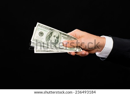 finances, people, savings and poverty concept - close up of male hand holding dollar cash money over black background