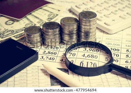 Financial accounting with pen, money, passport, mobile phone, magnifying glass and calculator