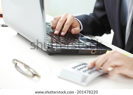 Financial adviser calculating data while working at bank. - stock photo