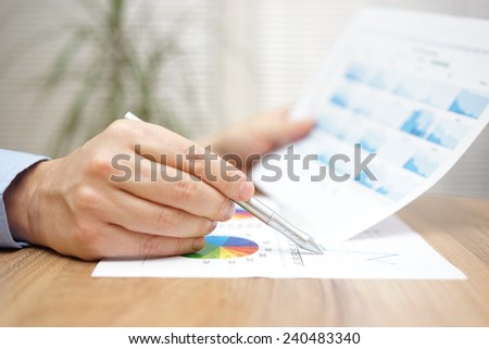 Financial adviser is reviewing report with charts and graphs - stock photo