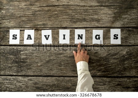 Financial adviser pointing to a Savings sign assembled with seven white cards on a textured rustic wooden desk. Conceptual of personal income, saving and consumerism. - stock photo