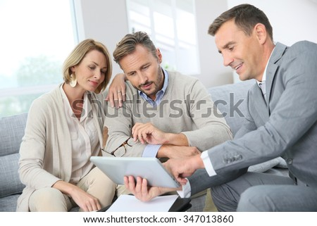 Financial adviser showing terms of contract on tablet - stock photo