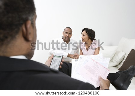 Financial adviser with forms and calculator in front of couple