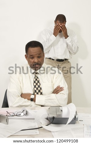 Financial adviser with tensed man in the background in the office - stock photo
