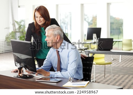 Financial advisor analyzing data with his colleagues while sitting at office and working on computer.