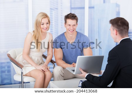 Financial advisor explaining investment plan to young couple on laptop in office