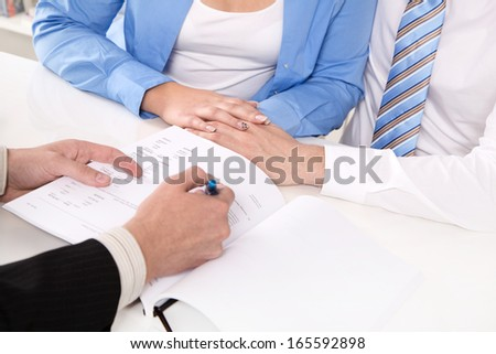 Financial Advisor is explaining a contract - young couple - stock photo