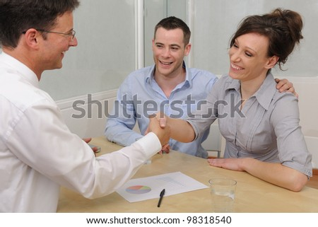 Financial advisor or lawyer giving advice to happy couple - stock photo