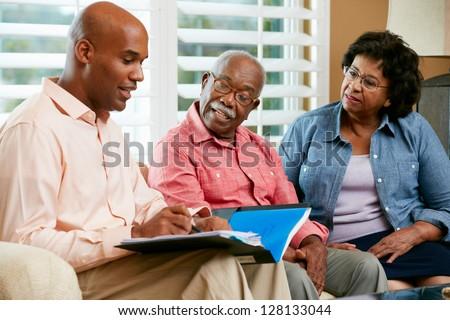 Financial Advisor Talking To Senior Couple At Home - stock photo