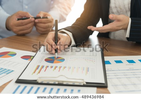 Financial advisor team are analyzing return on investment from business charts report.  Concept of financial planning, accounting and data analysis.
