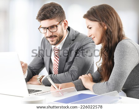 Financial advisors analyzing data on laptop while sitting at office.  - stock photo