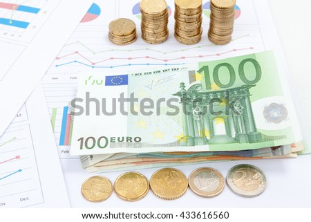 Financial and business chart and graphs, Euro money coin and 100 banknotes - stock photo
