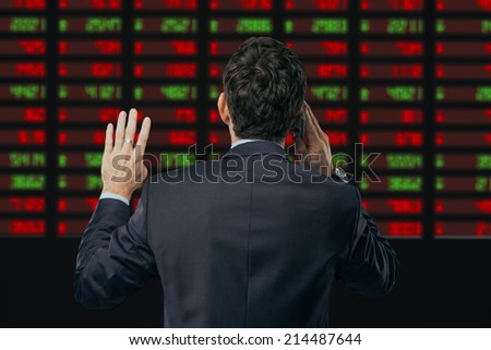 Financial broker looking at the electronic stock exchange board and talking on the phone, rear view - stock photo