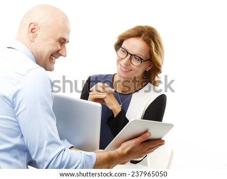 Financial businessman holding digital tablet and giving advise to sales woman while sitting against white background. Teamwork. - stock photo