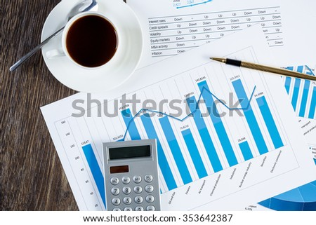 financial charts and graphs and a cup of coffee