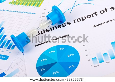 Financial charts and graphs. Sales report on paper. Hourglass. The countdown profits - stock photo