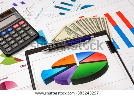 Financial charts on clipboard with calculator and money