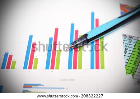 financial charts on table and blue pen
