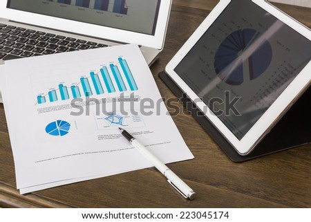 Financial charts on the table with tablet and laptop - stock photo
