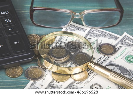 Financial concept. Calculator, magnifying glass, euro coins, british penny, dollar bills and glasses on green wood table.