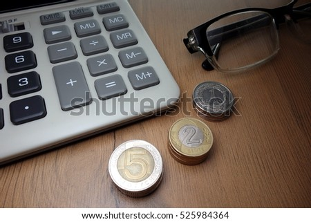 Financial concept - coins, calculator and eyeglasses