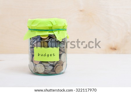 Financial concept. Coins in glass money jar with budget label. Wooden background - stock photo