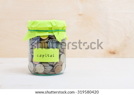 Financial concept. Coins in glass money jar with capital label. Wooden background - stock photo