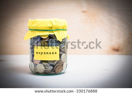 Financial concept. Coins in glass money jar with expenses label. Wooden background - stock photo