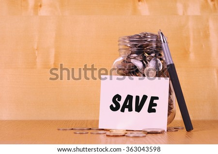 Financial concept. Coins in glass money jar with save label. Wooden background - stock photo