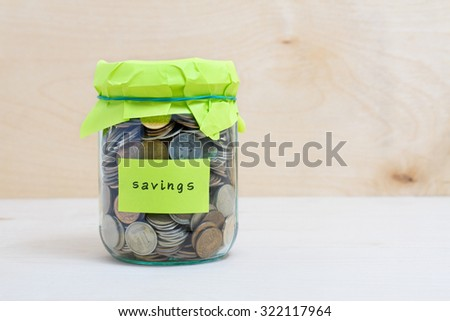 Financial concept. Coins in glass money jar with savings label. Wooden background - stock photo