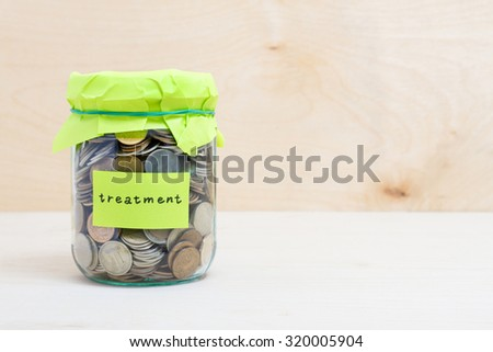 Financial concept. Coins in glass money jar with treatment label. Wooden background - stock photo