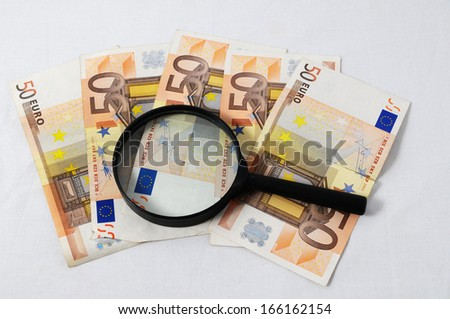 Financial Concept Loupe and Money on a White Background - stock photo