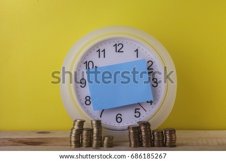 Financial Concept : Time is Money, Gold coin stacked with blue sticky note on clock