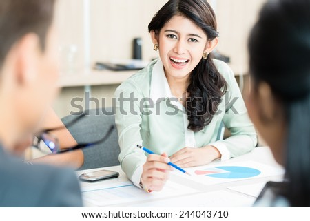 Financial consultant of Indonesian ethnicity in office discussing numbers - stock photo